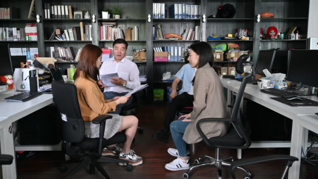 chinese business colleagues in impromptu office meeting - età miste video stock e b–roll