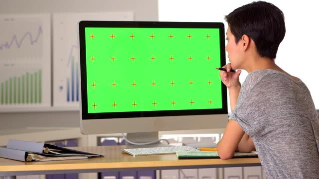 Chinese businesswoman analyzing green screen video