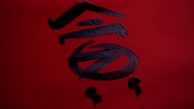vídeos de stock e filmes b-roll de chinese calligraphy. writing on red paper - japanese font