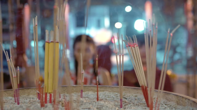 Chinese couple holding light incense stick and candle to pay respect in temple.