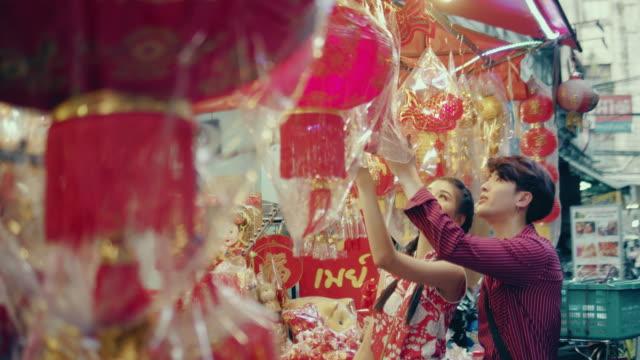 китайская пара покупки на уличном рынке. - китайский фонарь стоковые видео и кадры b-roll
