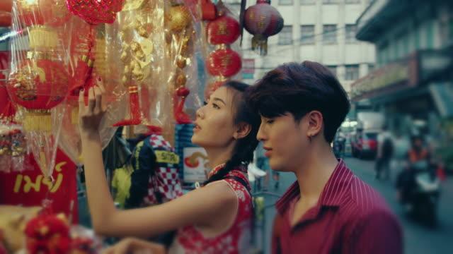 chińska para zakupy na rynku ulicznym. - chinese new year filmów i materiałów b-roll
