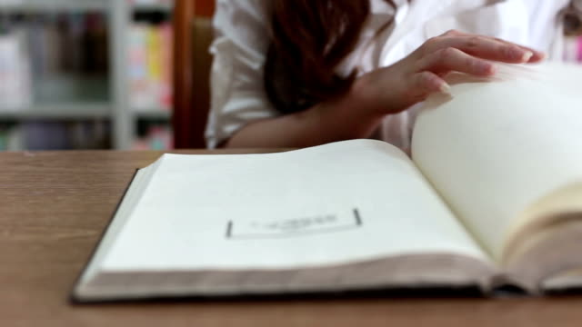 Chinese female student reading book in library,real time. video