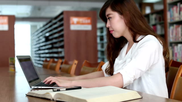 中国の女子学生のラップトップを使用して、ライブラリ、リアルタイム。 ビデオ