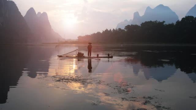 chinesische fischer werfen fischernetz bei sonnenaufgang - provinz guangxi stock-videos und b-roll-filmmaterial