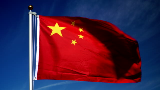 4K: China bandera en el asta de la bandera frente al aire libre Blue Sky (China) - vídeo