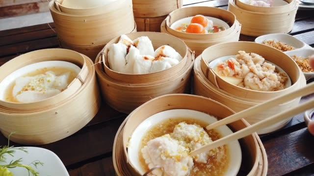 chinesisches essen. dampfende dim sum essen der sorte traditionell. asiatischer street food markt - kloß stock-videos und b-roll-filmmaterial