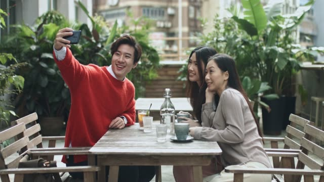 chinese friends taking a selfie at cafe terrace having drinks - terrazza video stock e b–roll