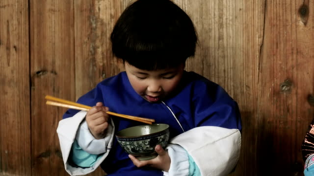 Chinese girl learning to eat with chopsticks from a bowl video