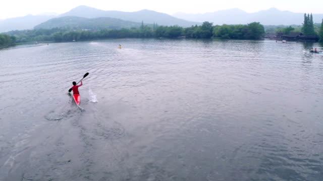 Chinese kayaking athlete practicing on lake, real time. video