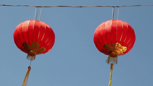 китайский фонарь движущихся в ветер с голубое небо. - китайский фонарь стоковые видео и кадры b-roll