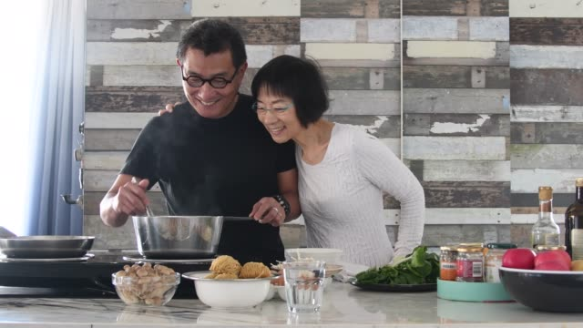 vídeos de stock e filmes b-roll de chinese man preparing meal with woman in kitchen - cooker happy