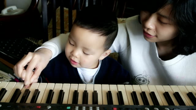Chinese mother and son having fun with keyboard with sound video