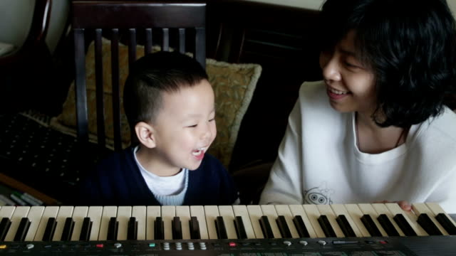 Chinese mother teaching her son how to play piano