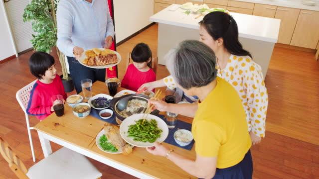 vídeos y material grabado en eventos de stock de familia china de múltiples generaciones comiendo años nuevos comida - comida china