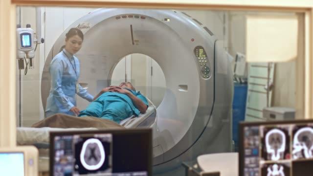 vídeos de stock e filmes b-roll de chinese nurse assisting patient during cat scan exam - tomografia