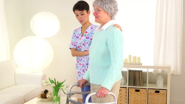 Chinese nurse helping elderly patient walk video