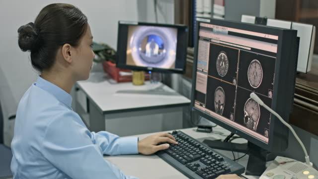 Chinese nurse radiologist using computer at MRI Scan Chinese nurse radiologist using computer at MRI Scan. radiologist stock videos & royalty-free footage