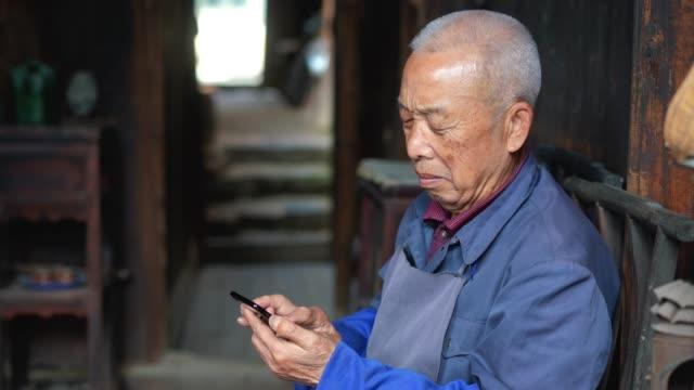 vídeos de stock e filmes b-roll de chinese senior man using mobile phone - cultura chinesa