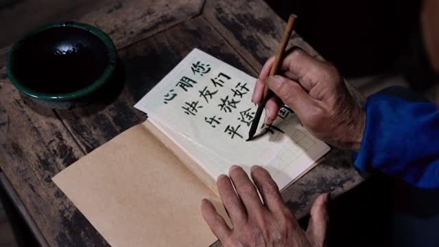 Chinese senior man writing chinese calligraphy