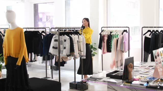Chinese shop assistant working in fashion boutique Mid adult woman hanging new clothes in clothes rails on shop floor, working in stylish department store, fashion, retail, organisation saleswoman stock videos & royalty-free footage