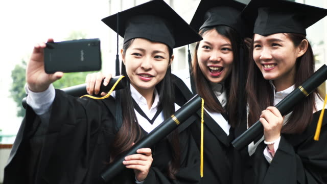 Chinese students taking selfies during graduation celebration.