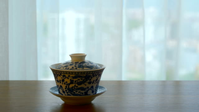 Chinese tea cup on table by window