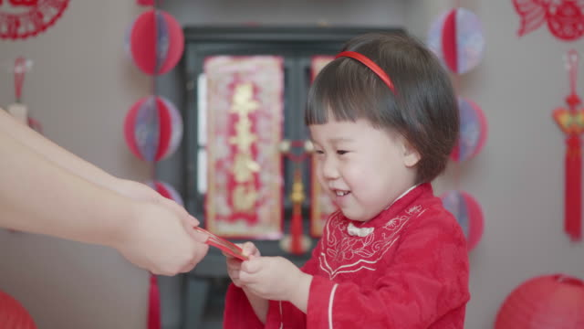 Chinese toddler girl celebrating Chinese new year get red envelop  at home Chinese toddler girl celebrating Chinese new year get red envelop  at home chinese new year stock videos & royalty-free footage
