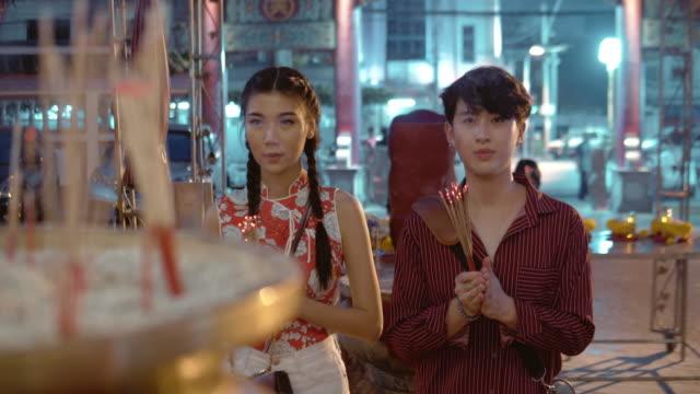 chiński turysta modląc się w świątyni w bangkoku, tajlandia. - chinese new year filmów i materiałów b-roll