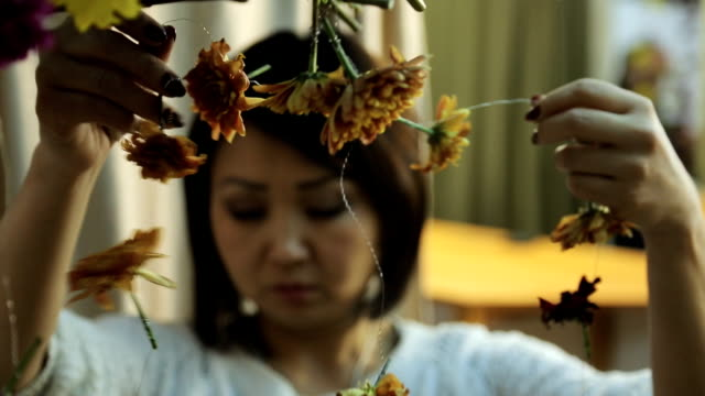 Chinese woman accurately hangs out floral decoration on wall video