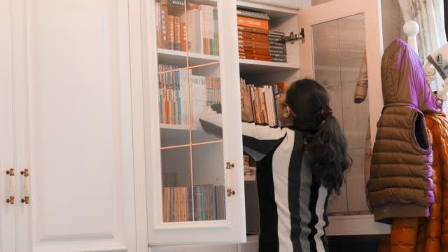 stockvideo's en b-roll-footage met chinese vrouw regelt boekenplank - boekenkast