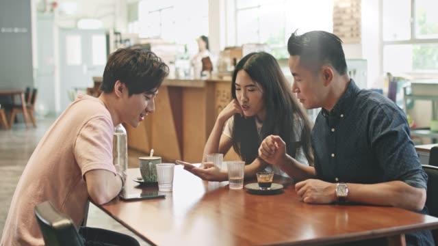 chinesin teilt soziale medien auf ihrem handy an ihre freunde in der cafeteria - chinesischer abstammung stock-videos und b-roll-filmmaterial