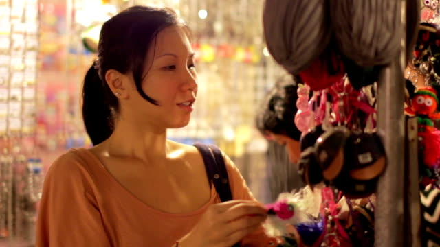 Chinese Young Woman Shopping at asian night market Chinese Young Woman Shopping at asian night market souvenir stock videos & royalty-free footage