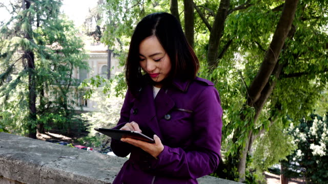 Chinese young Woman Using Digital Tablet And Smiling- outdoor video