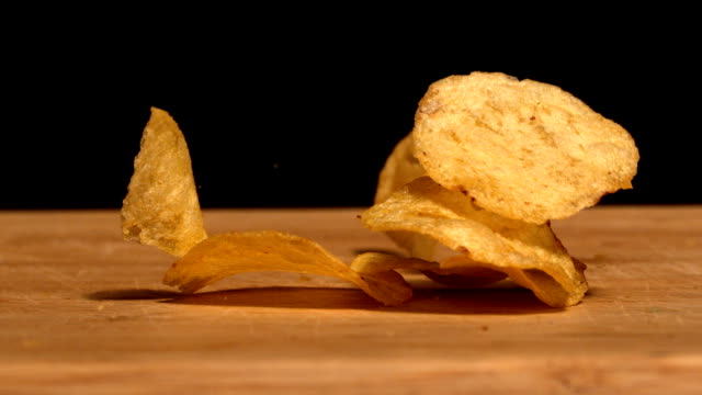 Chips falling on wooden table Chips falling on wooden table in slow motion potato chip stock videos & royalty-free footage
