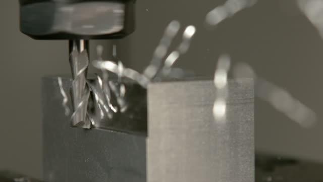 makro: chips av överskott av metall kommer flygande av ett arbetsstycke under pinnfräsning - cnc maskin bildbanksvideor och videomaterial från bakom kulisserna