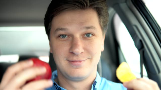 Chips or an apple. A man is eating an apple in a car. video