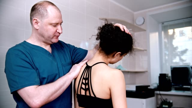 chiropractic treatment - the doctor inspecting the young woman from the back before the session - physical therapy стоковые видео и кадры b-roll