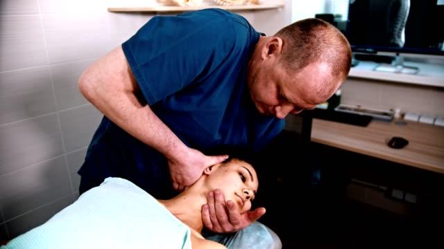 カイロプラクティック治療 - 女性患者に穏やかな首のマッサージを与える医師の専門家 - 両側に首を曲げる - 首点の映像素材/bロール