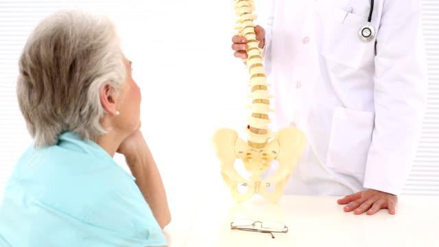 Chiropractor explaining spine model to patient video