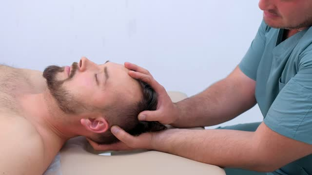 Chiropractor pressing on patient's neck in clinic on rehabilitation therapy. video