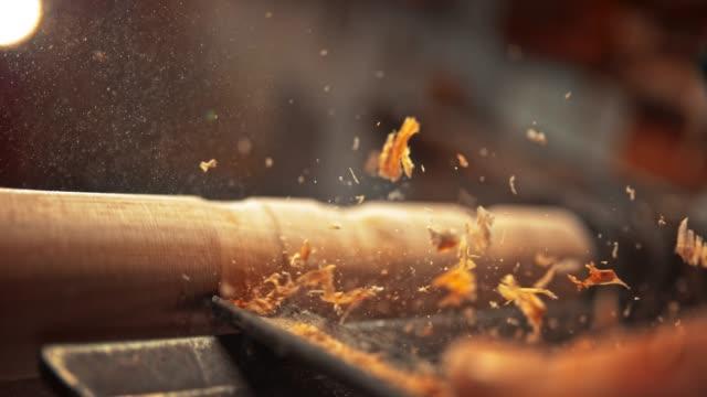 slo mo chisel wird verwendet, um ein stück holz zu schmücken und partikel fliegen in der luft - schreiner stock-videos und b-roll-filmmaterial