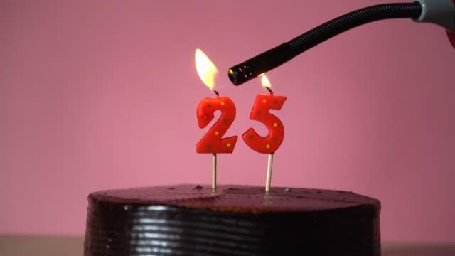 schokolade geburtstagstorte mit docht beleuchtung versucht, kerze zu sprengen - zahl 25 stock-videos und b-roll-filmmaterial