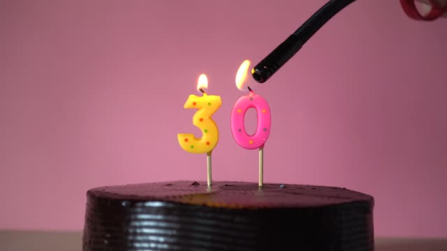 Chocolate birthday cake with wick lighting trying to blowout candle