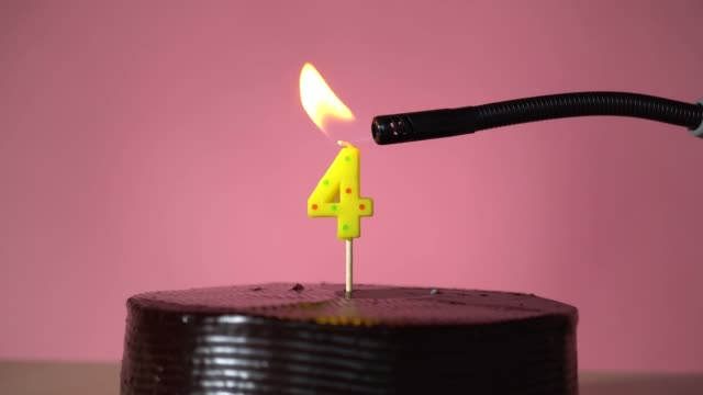 Chocolate birthday cake with wick lighting trying to blowout candle Chocolate birthday cake on pink background with yellow number four candle in middle electric lighter lighting candle making wish trying to blow out candle circa 4th century stock videos & royalty-free footage
