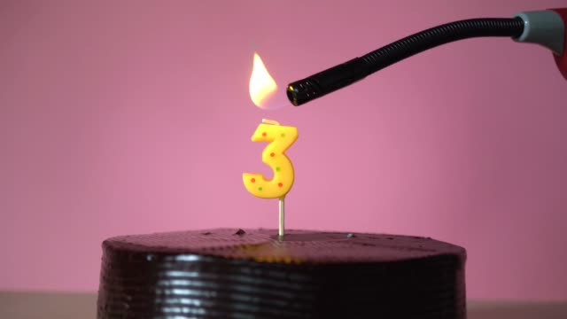 vídeos de stock e filmes b-roll de chocolate birthday cake with wick lighting trying to blowout candle - terceira