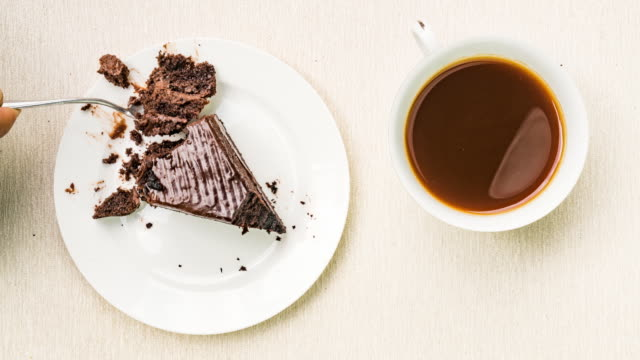 Chocolate cake in white ceramic plate on a wooden board Chocolate cake in white ceramic plate on a wooden board, Stop Motion snack stock videos & royalty-free footage