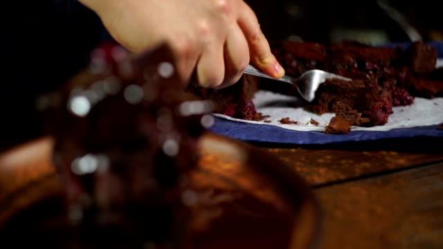 choklad tårta. män provsmakning bit av söta kakan. brownie kaka med cherry berry - brownie bildbanksvideor och videomaterial från bakom kulisserna