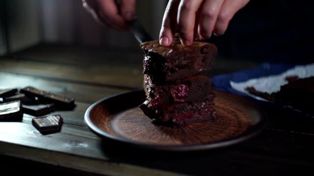 choklad tårta bitar. man hand sätta bit chokladkaka på plattan - brownie bildbanksvideor och videomaterial från bakom kulisserna