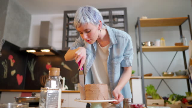 Chocolate cakes are her specialty Young woman making a cake at her kitchen. blue hair stock videos & royalty-free footage